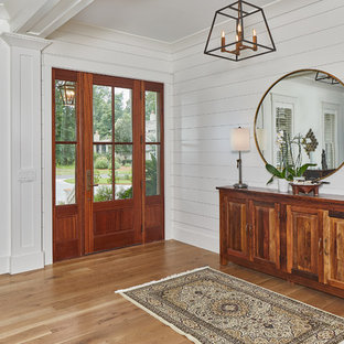 Entryway - mid-sized beach style light wood floor entryway idea in Charleston with white walls and a glass front door