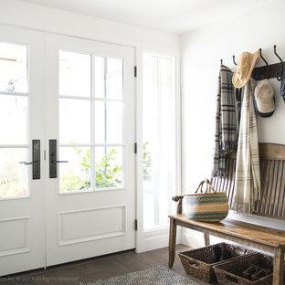 Modelo de distribuidor actual, de tamaño medio, con paredes blancas, suelo de madera en tonos medios, puerta doble y puerta blanca