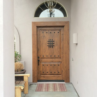 Inspiration for a large mediterranean concrete floor entryway remodel in Phoenix with purple walls and a medium wood front door