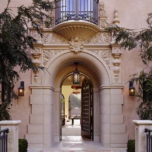 На фото: огромная прихожая в средиземноморском стиле с полом из терракотовой плитки и одностворчатой входной дверью с
