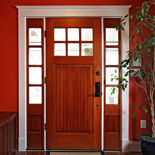 Foto de puerta principal tradicional, de tamaño medio, con paredes rojas, puerta simple, puerta de madera en tonos medios y suelo de madera en tonos medios