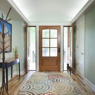 Cette image montre une entrée design avec un mur vert, une porte simple et une porte en bois brun.