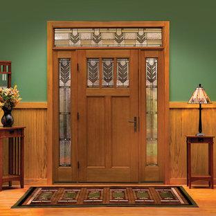 Cette image montre une porte d'entrée craftsman de taille moyenne avec un mur vert, un sol en bois clair, une porte simple et une porte en bois brun.
