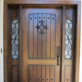 Cette photo montre un hall d'entrée méditerranéen avec une porte simple et une porte en bois brun.