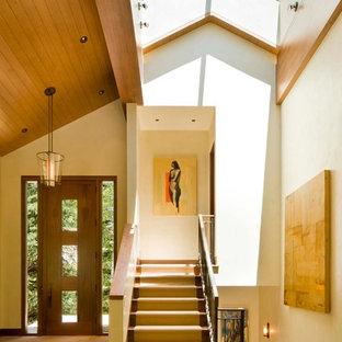 Cette photo montre un hall d'entrée chic avec un mur beige, une porte simple et une porte en bois foncé.