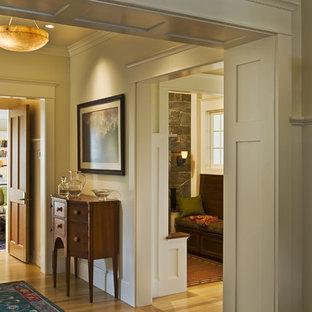 Bild på en vintage entré, med beige väggar och ljust trägolv