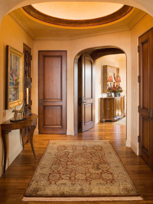 Inspiration for a mid-sized mediterranean medium tone wood floor entryway remodel in Minneapolis with & Cross Buck Door | Houzz