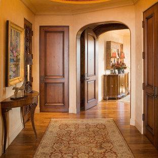 На фото: фойе среднего размера в средиземноморском стиле с бежевыми стенами, паркетным полом среднего тона, одностворчатой входной дверью и входной дверью из темного дерева