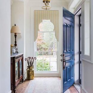 Idéer för en mellanstor klassisk foajé, med vita väggar, mörkt trägolv, en enkeldörr, en blå dörr och brunt golv