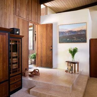 サンタバーバラの中サイズの両開きドアミッドセンチュリースタイルのおしゃれな玄関ドア (白い壁、トラバーチンの床、濃色木目調のドア) の写真