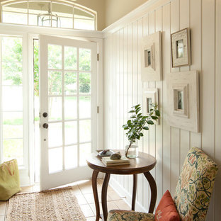 Ispirazione per una porta d'ingresso stile marinaro di medie dimensioni con una porta in vetro, pareti beige, pavimento con piastrelle in ceramica, una porta singola e pavimento beige
