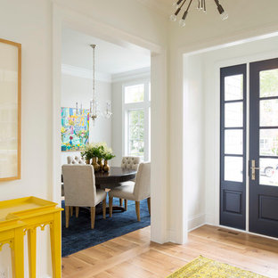 Inredning av en modern mellanstor foajé, med vita väggar, ljust trägolv, en enkeldörr, en blå dörr och brunt golv