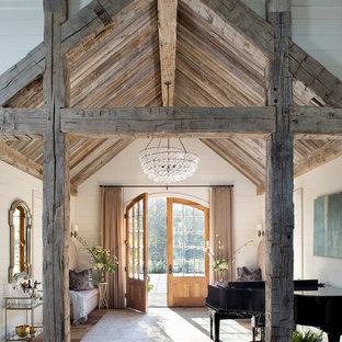 オースティンの両開きドアカントリー風おしゃれな玄関ロビー (白い壁、無垢フローリング、木目調のドア、茶色い床) の写真