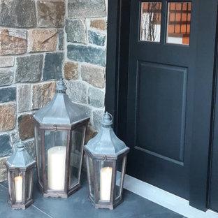 広い両開きドアコンテンポラリースタイルのおしゃれな玄関ドア (青い壁、コンクリートの床、黒いドア、レンガ壁) の写真