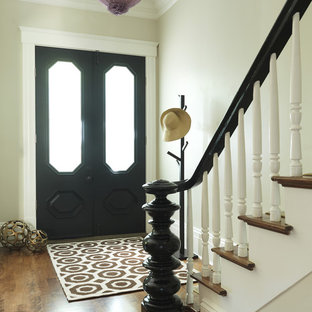 Example of a classic medium tone wood floor double front door design in Boston with beige walls and a black front door