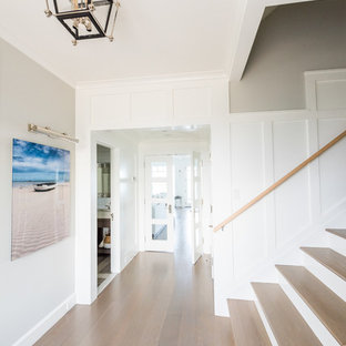 Example of a mid-sized beach style light wood floor and beige floor entryway design in New York with gray walls