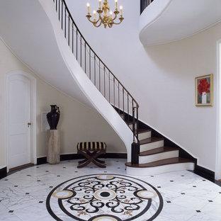 サンタバーバラの巨大なトラディショナルスタイルのおしゃれな玄関ロビー (ベージュの壁、大理石の床) の写真