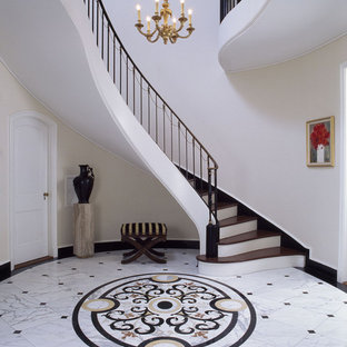 Réalisation d'un très grand hall d'entrée tradition avec un mur beige et un sol en marbre.