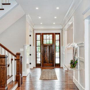 Immagine di un grande ingresso tradizionale con pareti bianche, parquet scuro, una porta singola, una porta in legno scuro e pavimento marrone