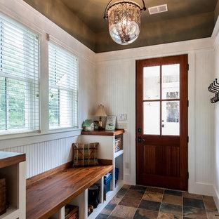 Idéer för ett mellanstort klassiskt kapprum, med travertin golv, mellanmörk trädörr, vita väggar och en enkeldörr