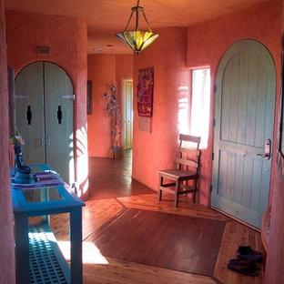 ソルトレイクシティの中サイズの片開きドアサンタフェスタイルのおしゃれな玄関ロビー (ピンクの壁、淡色無垢フローリング、緑のドア、茶色い床) の写真