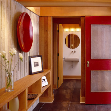 Entry with tile floors, board formed concrete and red door