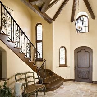 他の地域の片開きドアコンテンポラリースタイルのおしゃれな玄関ロビー (ベージュの壁、濃色木目調のドア、トラバーチンの床、ベージュの床) の写真