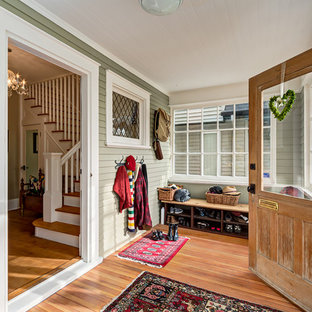 Inspiration for a mid-sized cottage medium tone wood floor entryway remodel in Calgary with green walls and a medium wood front door