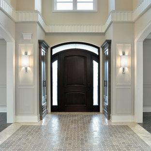 Klassisk inredning av en entré, med mörk trädörr och grått golv