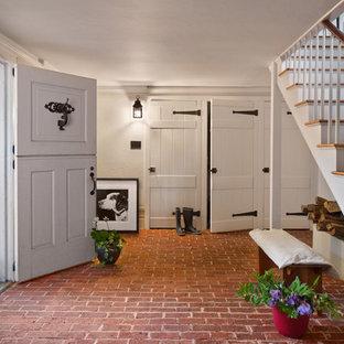 Foto de distribuidor de estilo de casa de campo con paredes blancas, suelo de ladrillo, puerta tipo holandesa y puerta blanca