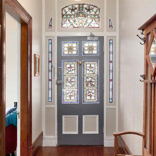This is an example of a traditional front door in Sydney with beige walls, medium hardwood floors, a single front door, a gray front door and brown floor.