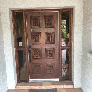 Foto di un piccolo ingresso o corridoio minimal con pareti grigie, una porta singola, una porta in legno bruno, pavimento con piastrelle in ceramica, pavimento grigio e boiserie
