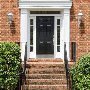 Свежая идея для дизайна: входная дверь среднего размера в классическом стиле с одностворчатой входной дверью, черной входной дверью и красными стенами - отличное фото интерьера