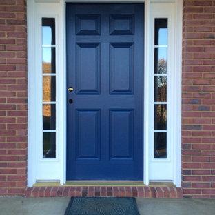 На фото: входные двери в современном стиле с красными стенами и синей входной дверью