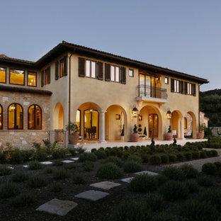 Неиссякаемый источник вдохновения для домашнего уюта: большая входная дверь в средиземноморском стиле с бежевыми стенами, полом из известняка, одностворчатой входной дверью и входной дверью из дерева среднего тона