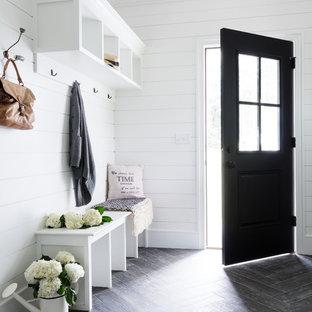 Стильный дизайн: маленький тамбур в стиле кантри с белыми стенами, полом из керамогранита, одностворчатой входной дверью, черной входной дверью и серым полом - последний тренд
