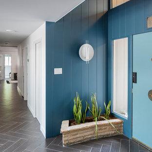 Réalisation d'une entrée vintage avec un couloir, un mur bleu, une porte simple, une porte bleue et un sol marron.