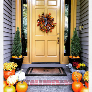 Bild på en mellanstor vintage ingång och ytterdörr, med bruna väggar, tegelgolv, en enkeldörr, en gul dörr och grått golv