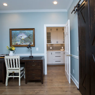 Inspiration for a mid-sized transitional medium tone wood floor and brown floor entryway remodel in Raleigh with blue walls and a white front door