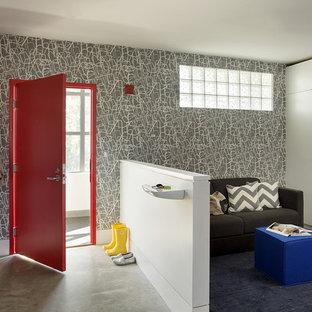 Exemple d'une entrée tendance de taille moyenne avec un vestiaire, un mur multicolore, béton au sol, une porte simple et une porte rouge.