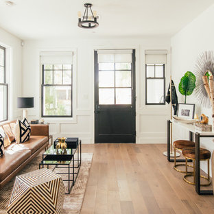 Example of a transitional medium tone wood floor and brown floor entryway design in Los Angeles with white walls and a black front door