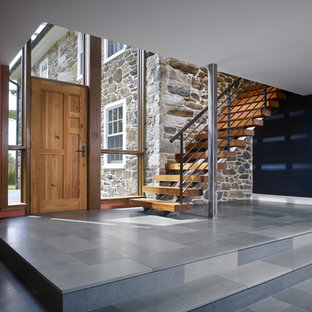 Example of a farmhouse limestone floor entryway design in Philadelphia with a medium wood front door