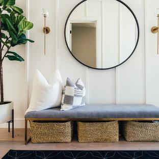 Inspiration för en lantlig entré, med vita väggar och ljust trägolv