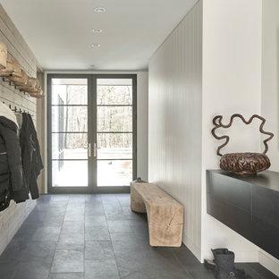 Cette photo montre un hall d'entrée nature en bois de taille moyenne avec un mur blanc, un sol en ardoise, une porte double, une porte noire et un sol gris.