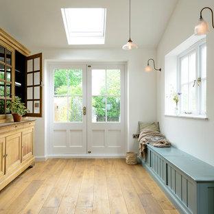 Diseño de vestíbulo posterior de estilo de casa de campo, de tamaño medio, con paredes blancas, suelo de madera clara, puerta doble, puerta blanca y suelo amarillo