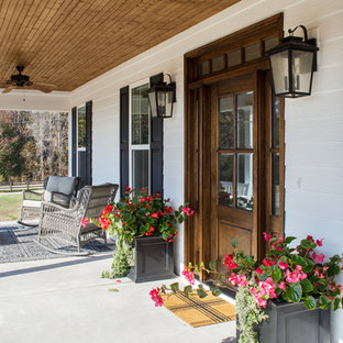Idées déco pour une porte d'entrée campagne de taille moyenne avec un mur blanc, béton au sol, une porte simple, une porte en bois foncé et un sol blanc.