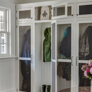 Inspiration for a mid-sized timeless medium tone wood floor mudroom remodel in Boston with white walls