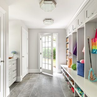 Transitional gray floor entryway photo in New York with gray walls and a glass front door