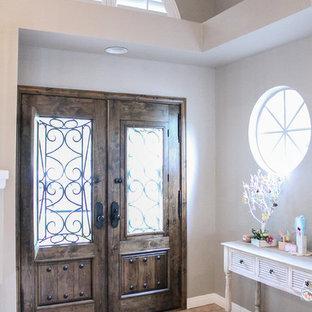 Mittelgroße Shabby-Look Haustür mit grauer Wandfarbe, Travertin, Einzeltür und dunkler Holztür in Los Angeles