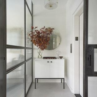 Idee per un piccolo ingresso minimalista con pareti bianche, pavimento in cemento, una porta scorrevole, una porta nera e pavimento grigio